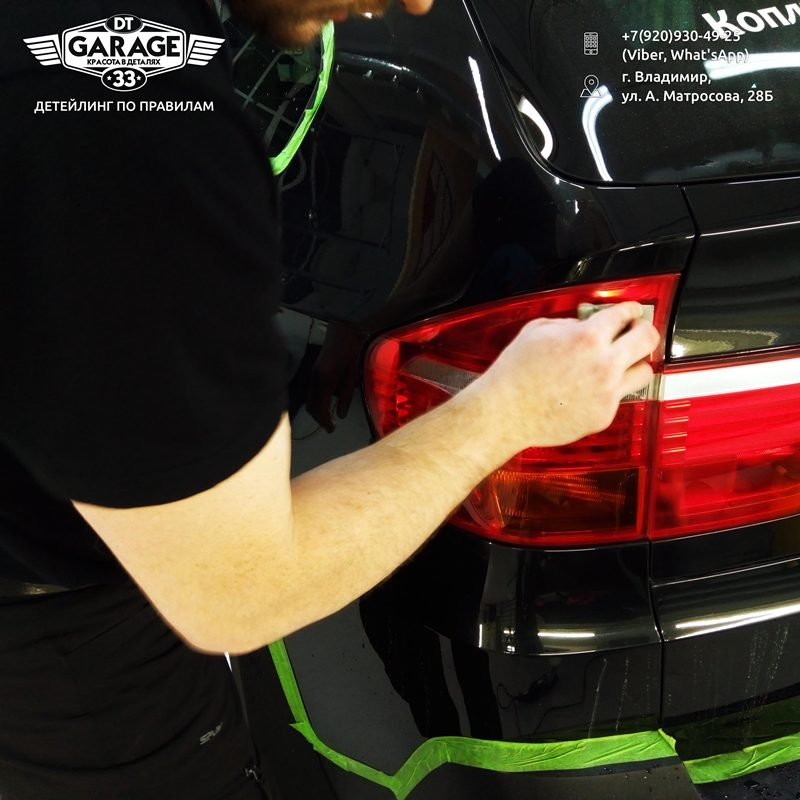 На фото мастер Сергей протирает задний фонарь автомобиля чистящим составом.