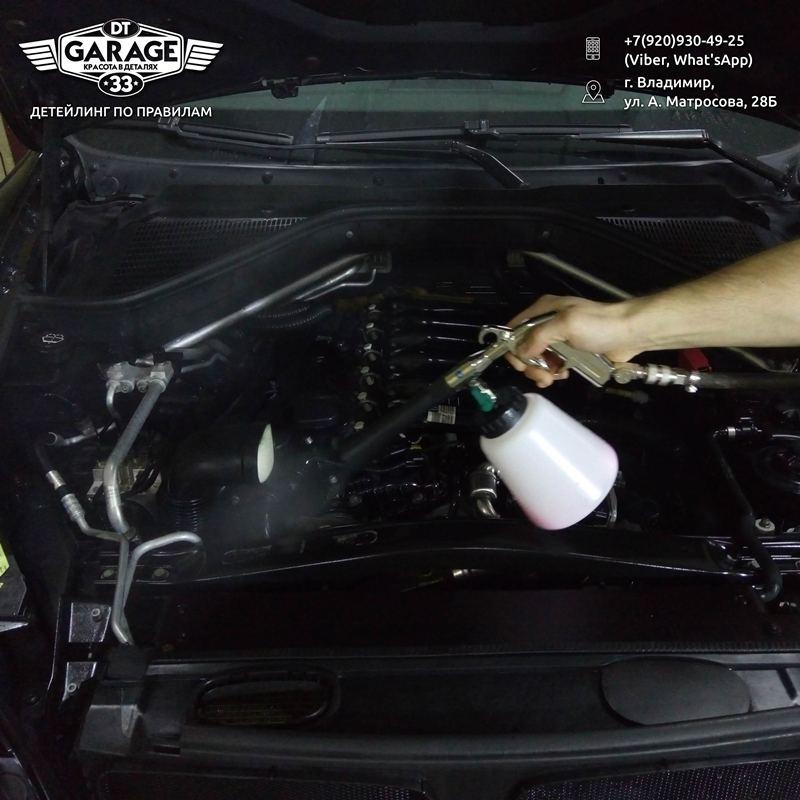 На фото мастер детейлинга DT GARAGE 33 обрабатывает двигатель и подкапотное пространство составом Motorplast