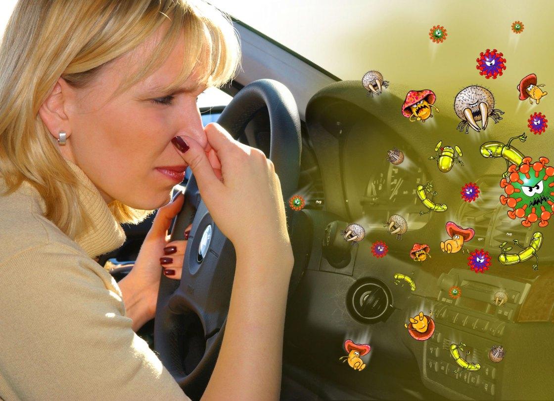 На фото девушка, которая морщится от запаха, идущего из кондиционера автомобиля.