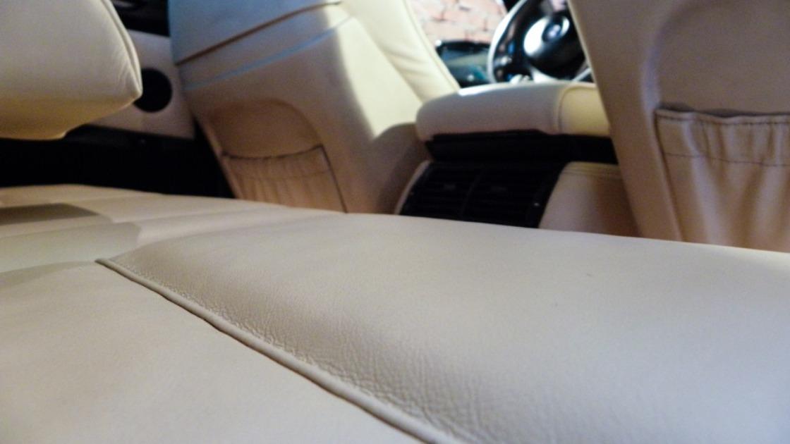 На фото крупным планом обработанная кожа салона автомобиля.