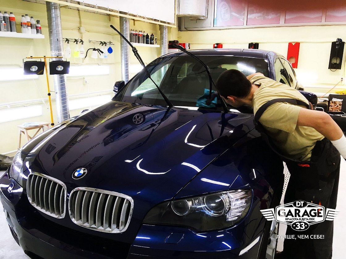 На фото мастер за работой. Он наносит состав «Антидождь» на лобовое стекло автомобиля BMW.
