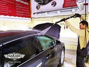 На фото мастер ателье «DT GARAGE 33» моет автомобиль перед полировкой.