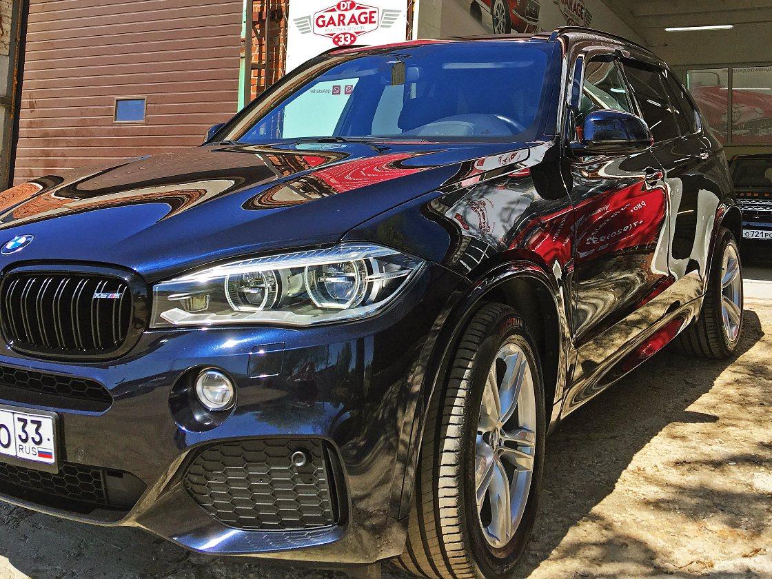 На фото автомобиль BMW X5 при естественном солнечном освещении.