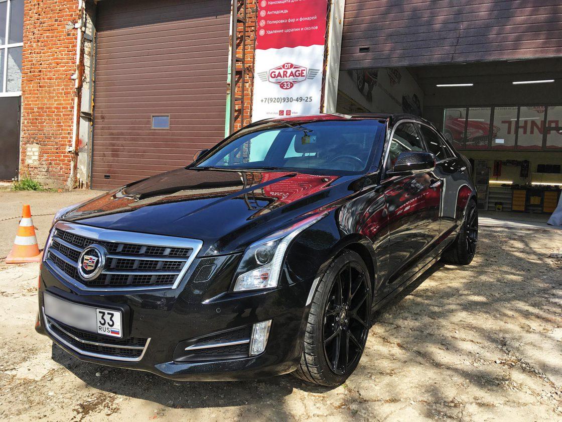 На фото Cadillac ATS при естественном дневном освещении. Владелец проверяет качество полировки.