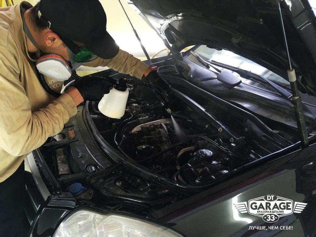На фото мастер детейлинга распыляется состав Golden Star на двигатель BMW.