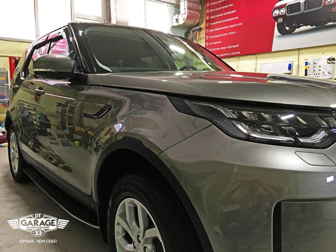 На фото крупным планом правый борт автомобиля Land Rover Discovery 5 с ярким отражением.