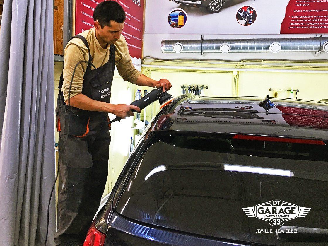 На фото мастер ателье «DT GARAGE 33» полирует крышу автомобиля BMW X5.