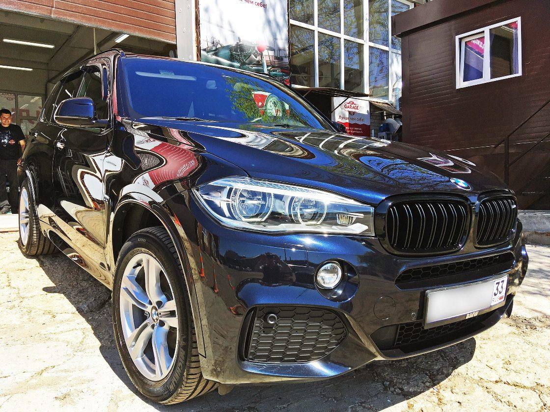 На фото капот и бампер BMW X5 крупным планом в ярком солнечном свете.