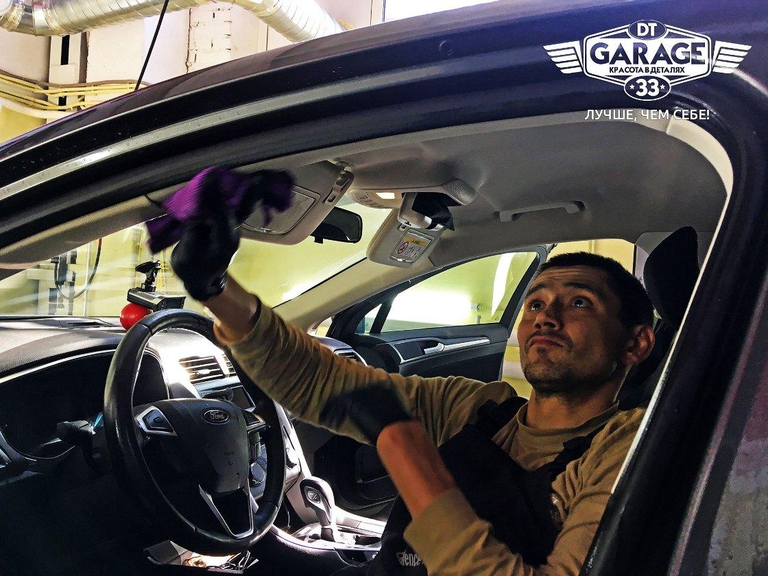 На фото мастер «DT GARAGE 33» чистит салон автомобиля Ford.