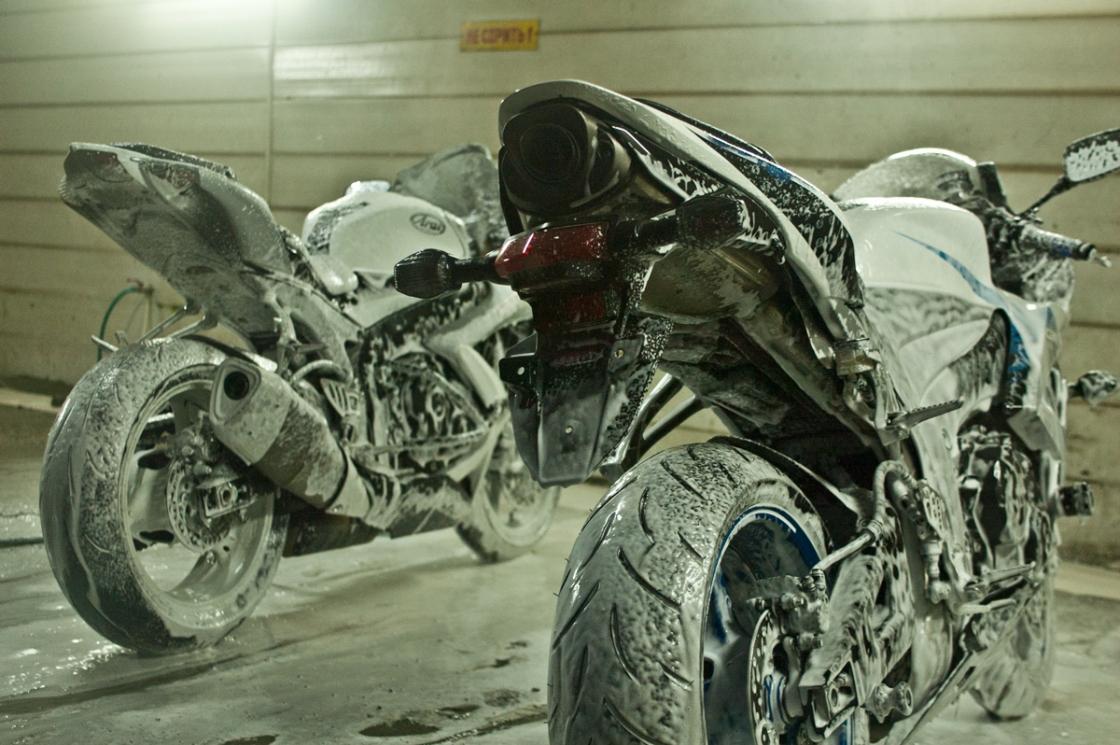 На фото выполняется удаление стойких загрязнений у мотоцикла.