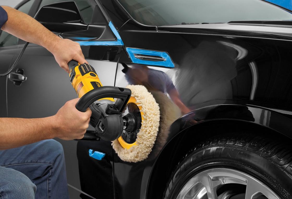 На фото мастер полирует автомобиль
