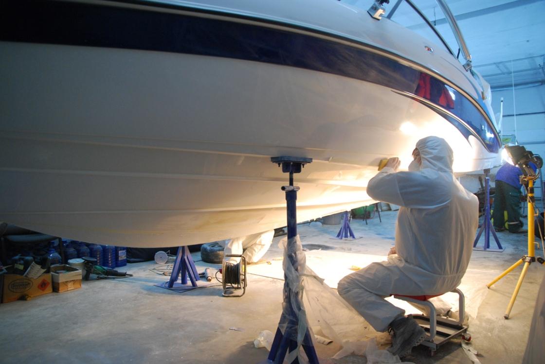 На фото мастер чистит днище лодки.