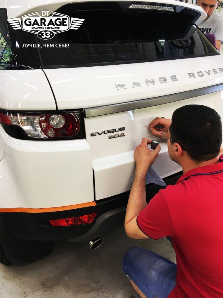 На фото мастер Артём делает ремонт сколов у автомобиля Range Rover Evoque.