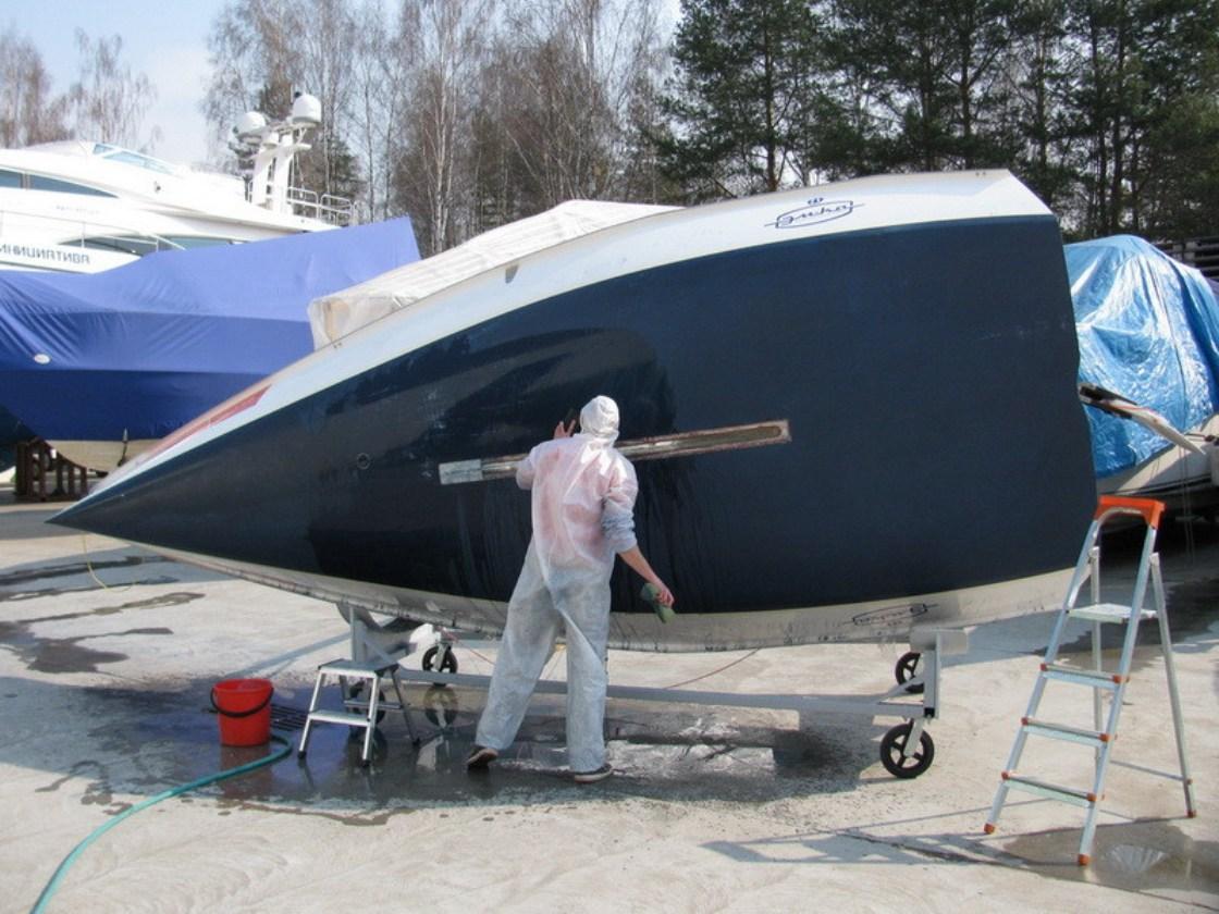 На фото мастер обрабатывает днище катера защитным составом.