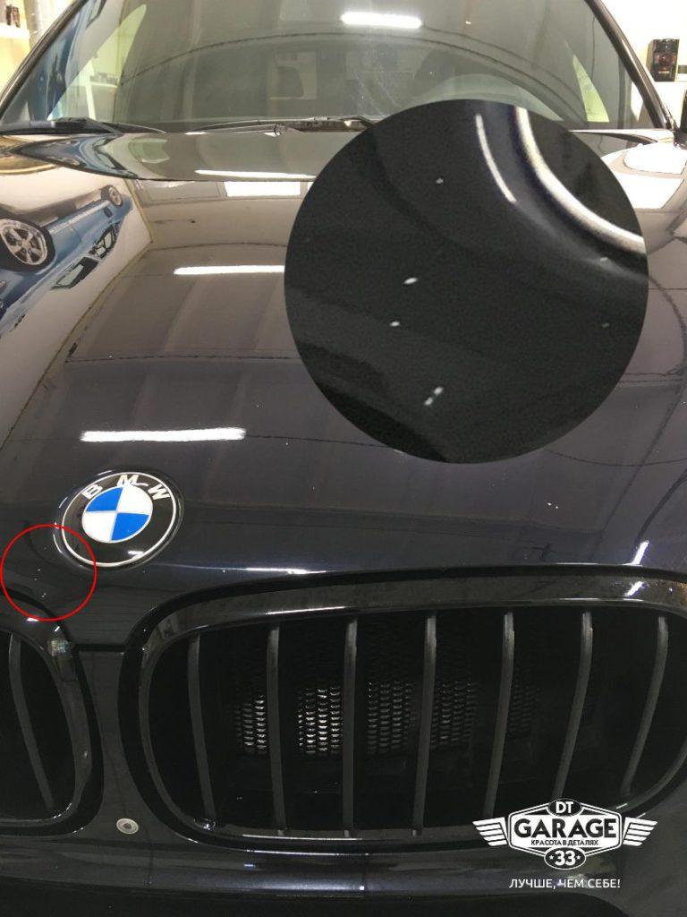 На фото крупным планом показаны сколы на капоте внедорожника БМВ.