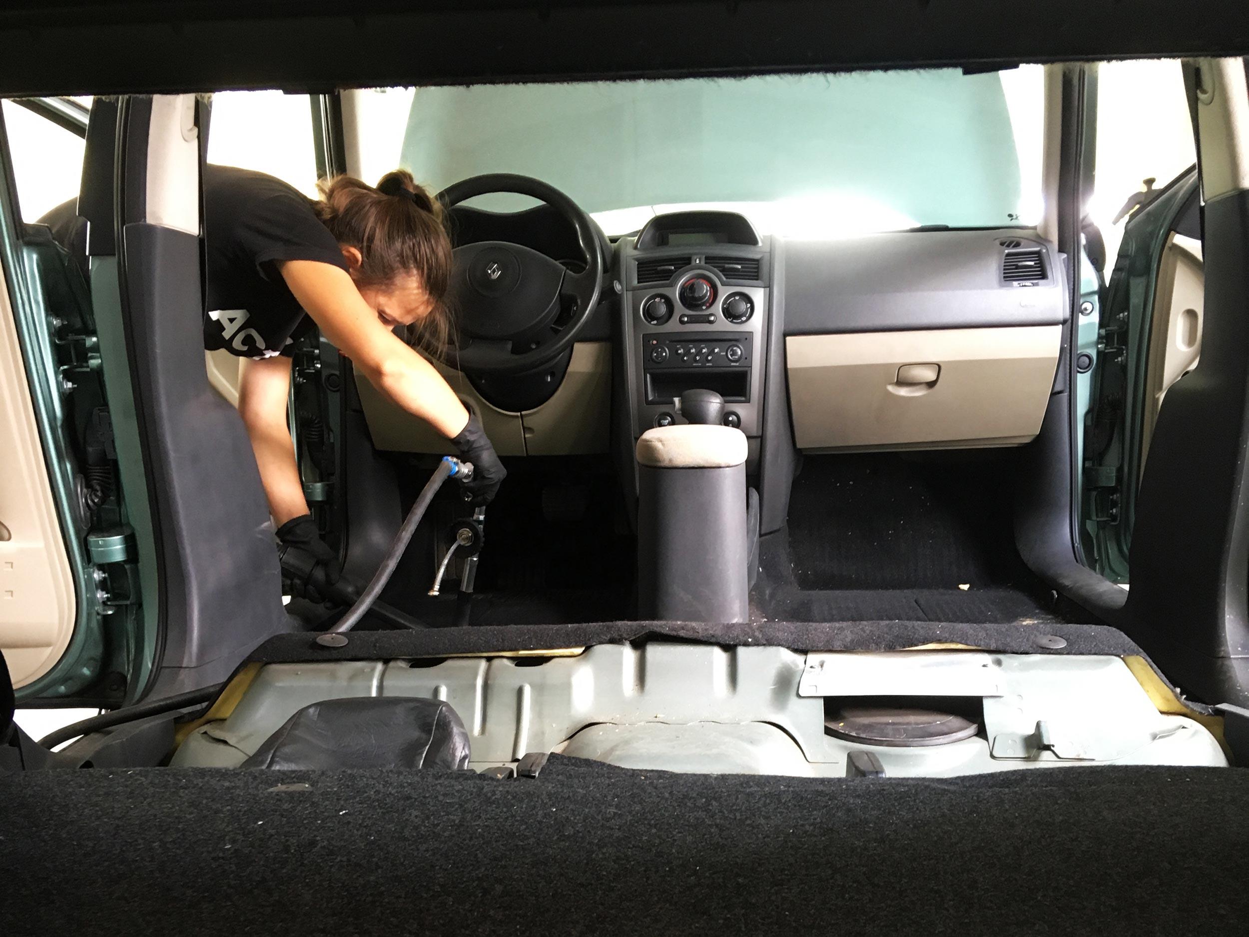 На фото девушка чистит салон автомобиля моющим пылесосом.