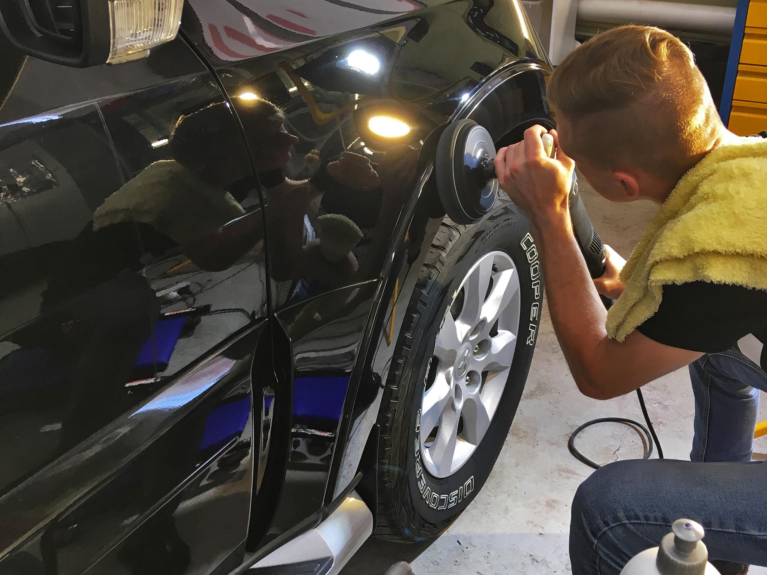 На фото процессе полировки. Мастер полирует автомобиль с использованием профессиональной полировальной машины