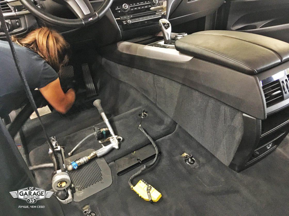 На фото мастер DT GARAGE 33 чистит место водителя.