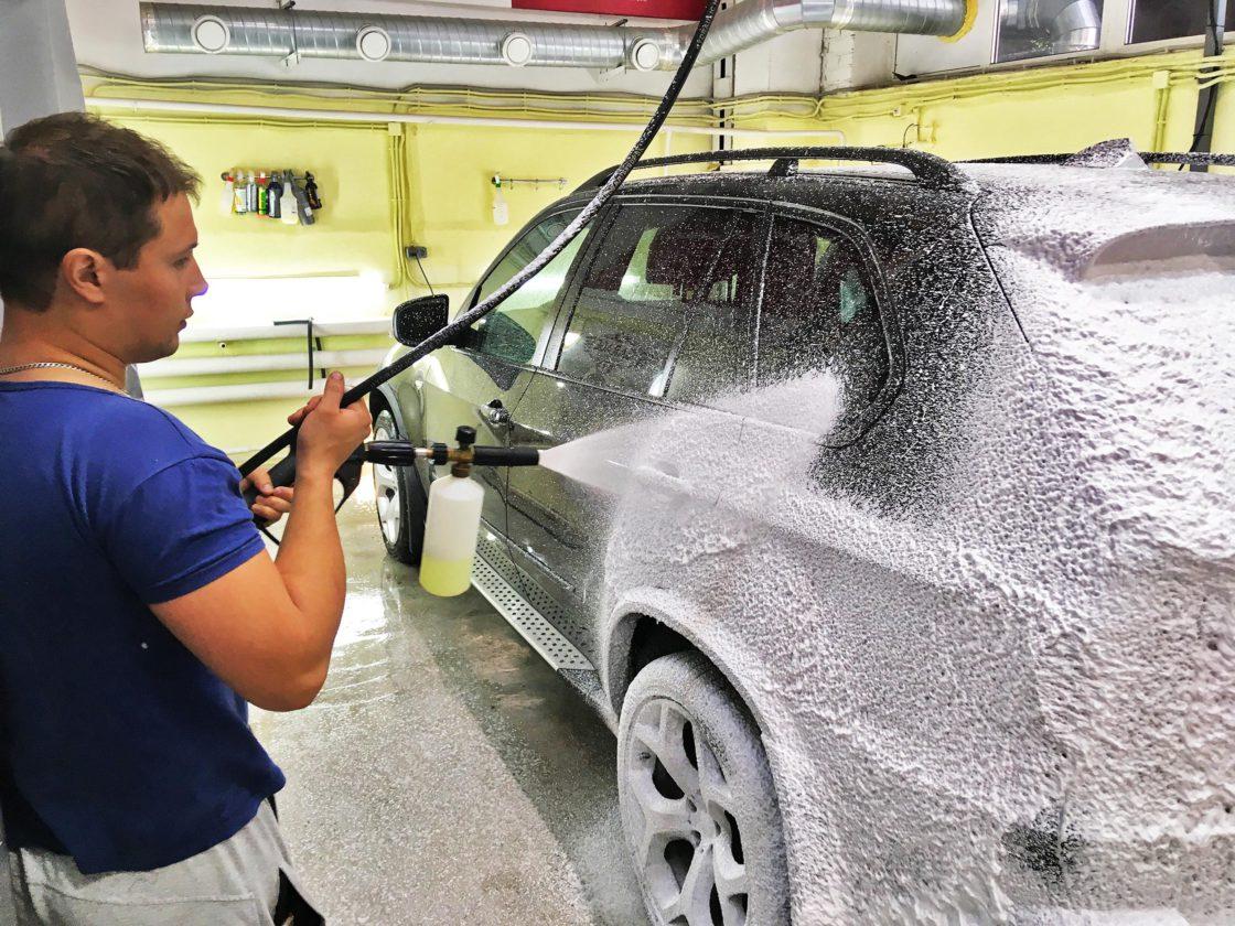 Мастер наносит на кузов машины пенный моющий состав