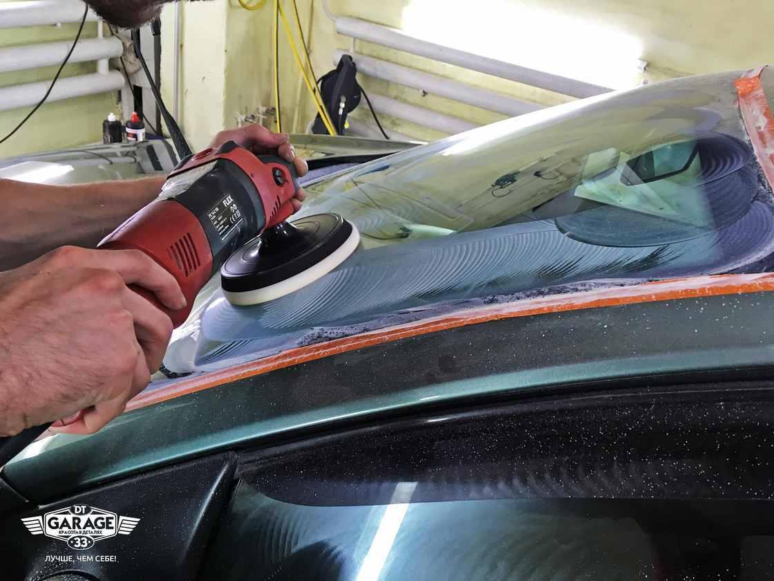 На фото мастер ателье «DT GARAGE 33» полирует стекло у автомобиля BMW.