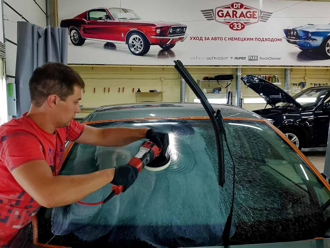На фото мастер ателье «DT GARAGE 33» полирует лобовое стекло у BMW