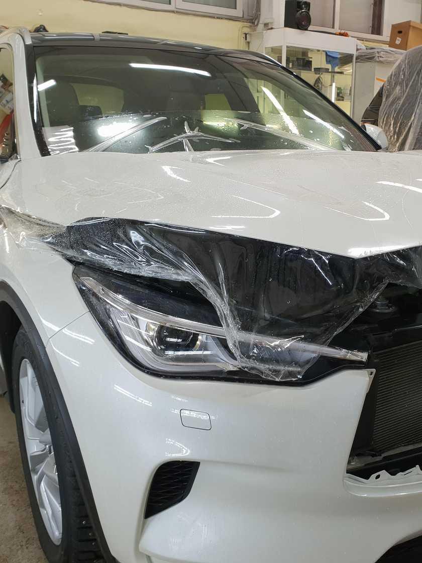 На фото процесс оклейки пленкой Suntek PPF капота автомобиля.