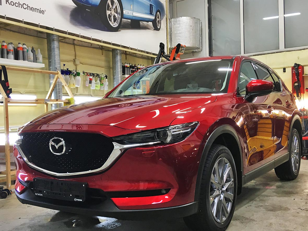 На фото автомобиль Мазда красного цвета с уже установленной антигравийной защитой.