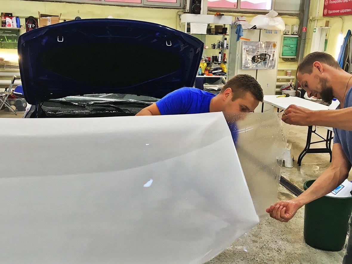 На фото технологи владимирского детейлинг-центра «DT GARAGE 33» готовят пленку PremiumShield к монтажу на автомобиль.