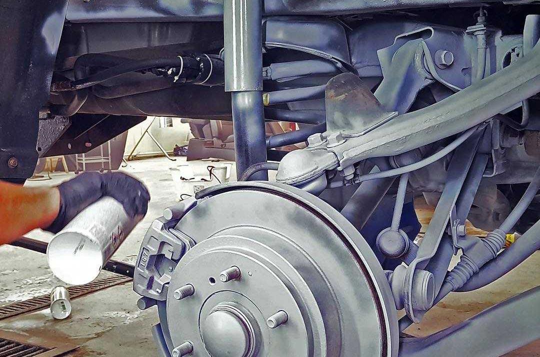 На фото процесс обработки подвески у Mitsubishi Pajero защитным составом.