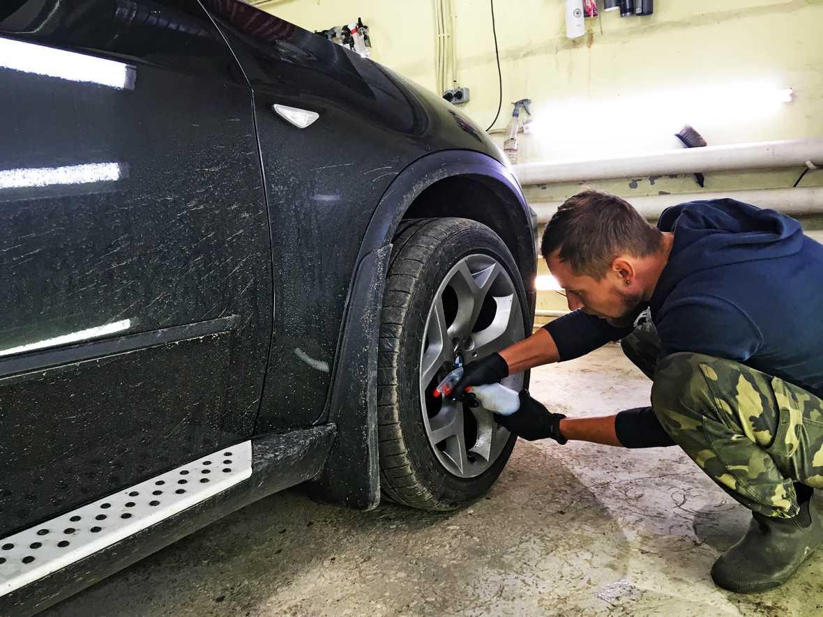На фото мастер обрабатывает колесо автомобиля реактивным составом, растворяющим металлическую пыль.