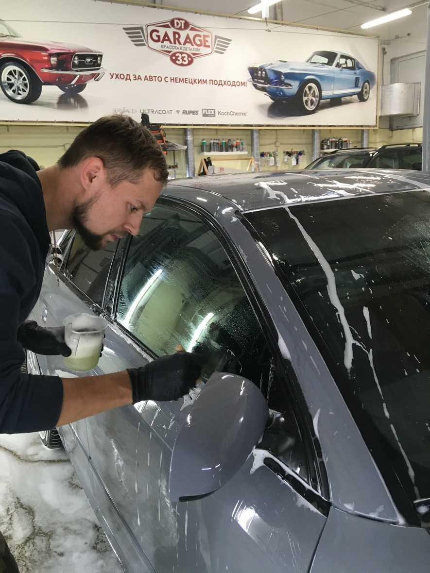 На фото мастер моет машину с помощью кисти.