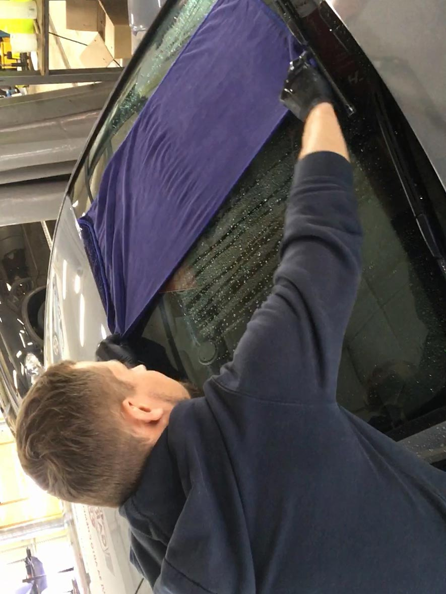 На фото мастер владимирского детейлинга сушит машину большим полотенцем.
