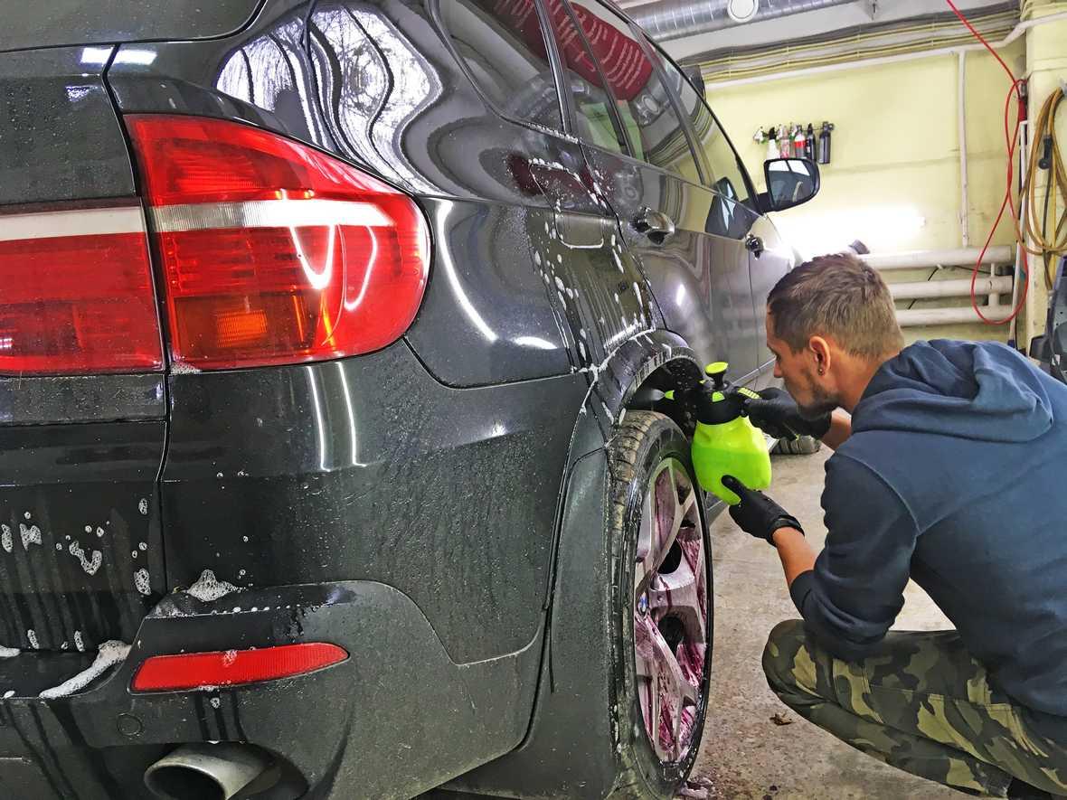 На фото мастер-технолог обрабатывает концентрированным моющим средством колесную арку у BMW X5.