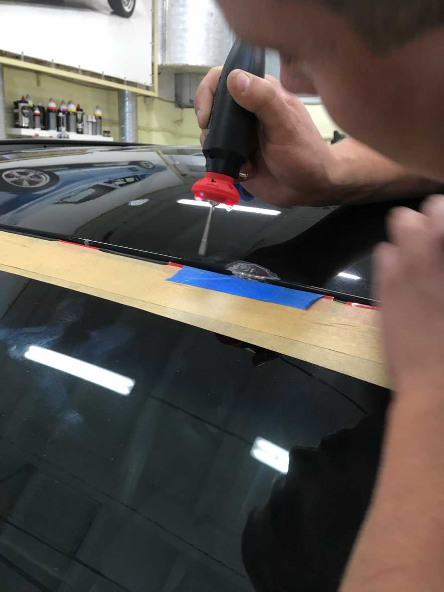 На фото мастер детейлинга за работой. Он зачищает металл от ржавчины на крыше Hyundai Santa Fe.