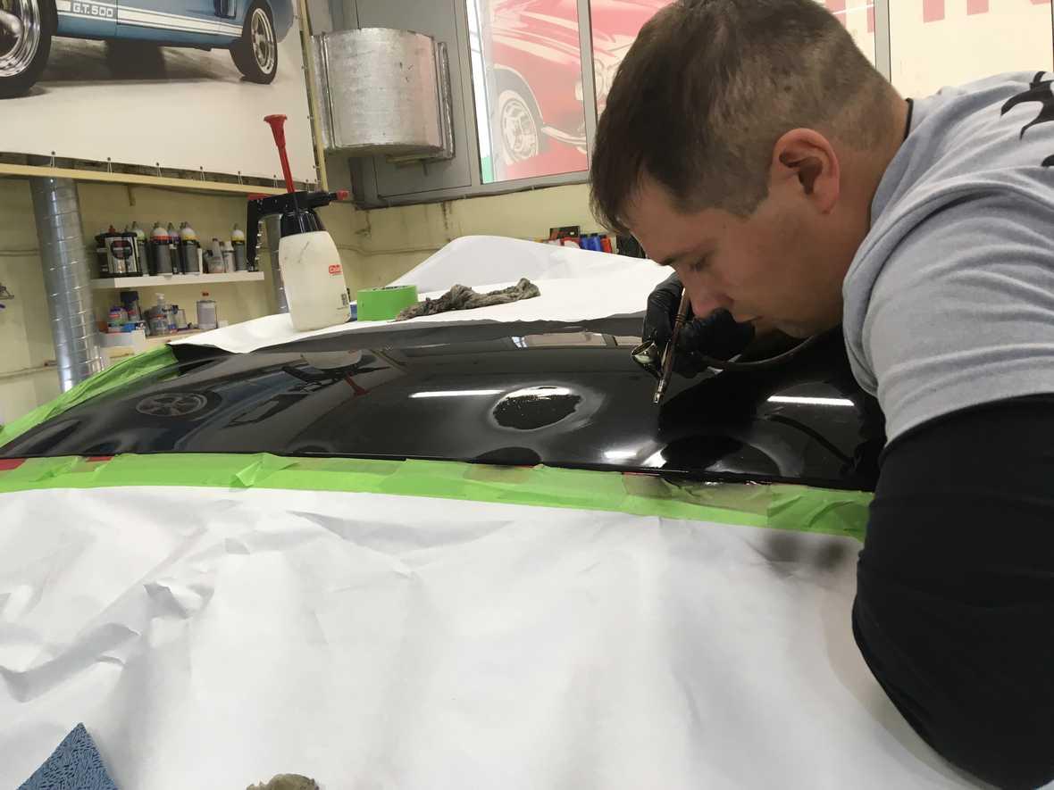 На фото мастер работает с аэрографом. Производится прокрашивание восстанавливаемого фрагмента.
