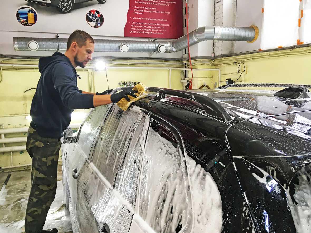 На фото мастер детейлинг-центра «DT GARAGE 33» выполняет ручную мойку BMW X5.