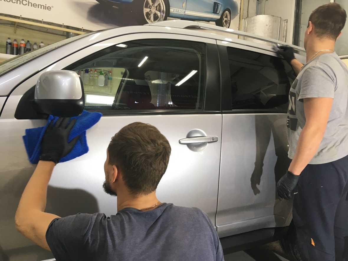 На фото два мастера «DT GARAGE 33» за работой. Они наносят жидкое стекло на Mitsubishi Outlander.