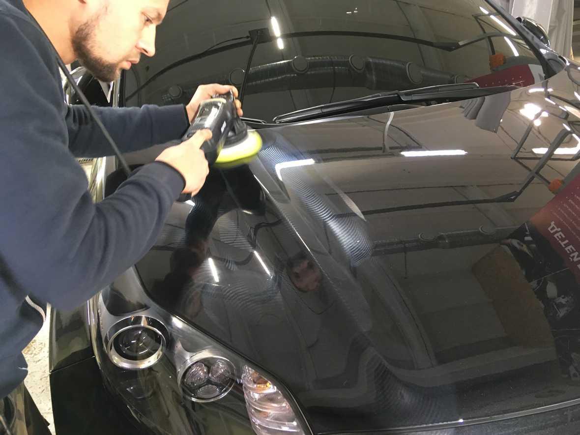 На фото мастер детейлинг-центра выполняет машинную легкую полировку автомобиля KIA.
