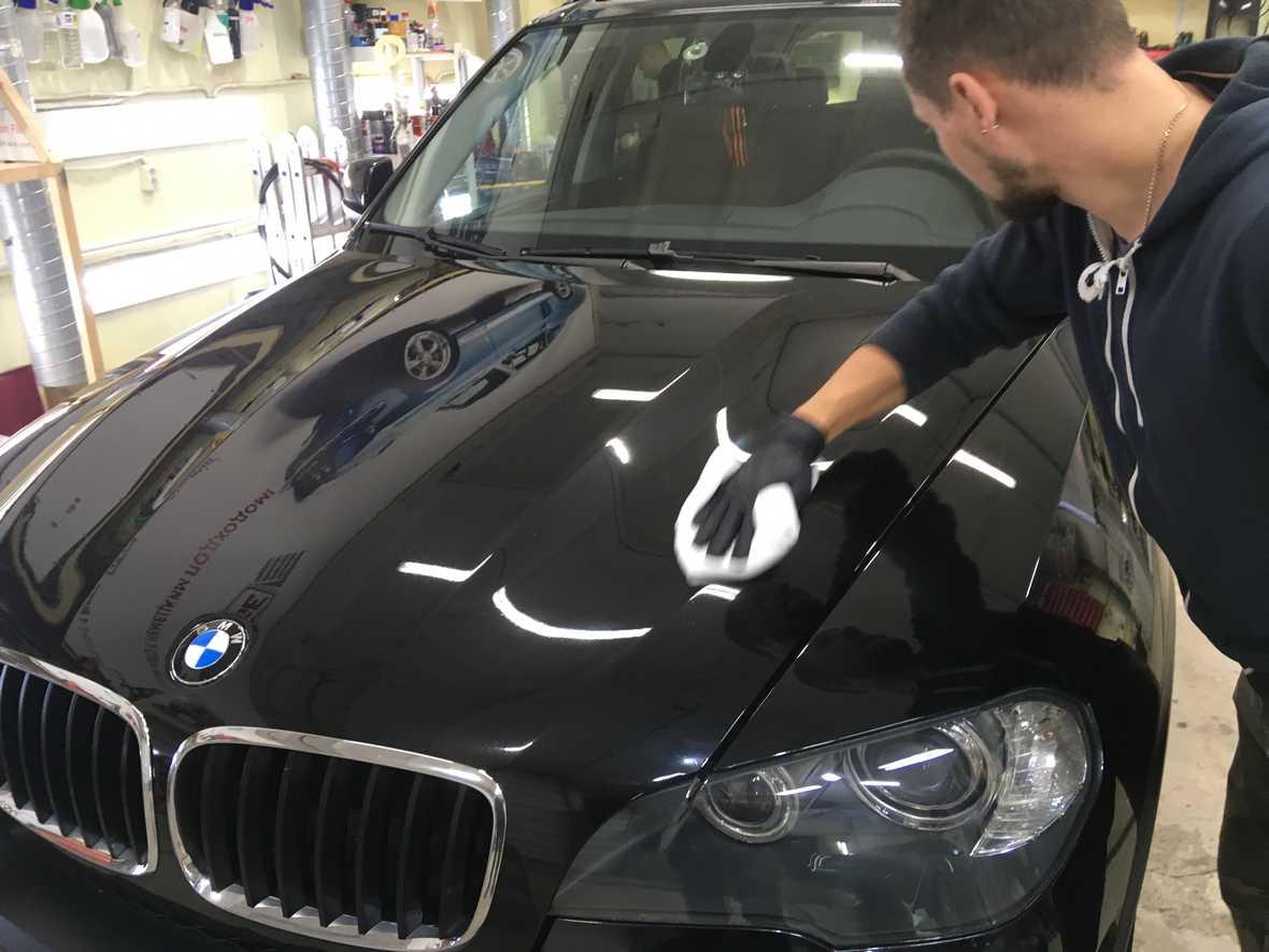 На фото мастер детейлинга «DT GARAGE 33» обрабатывает гидрофобом капот у автомобиля BMW.