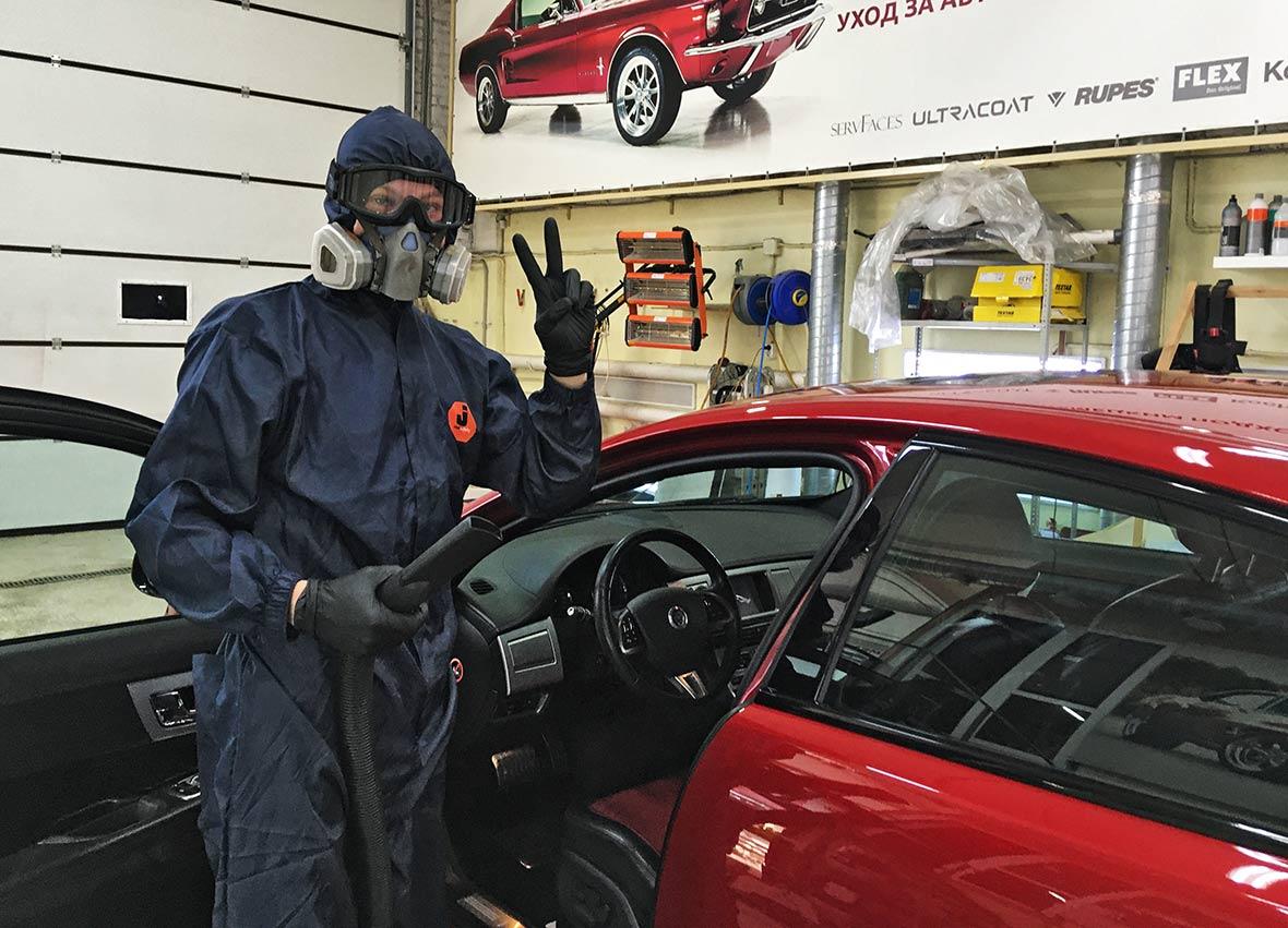Смотреть на фото мастер детейлинга DT GARAGE 33 делает химчистку салона автомобиля.