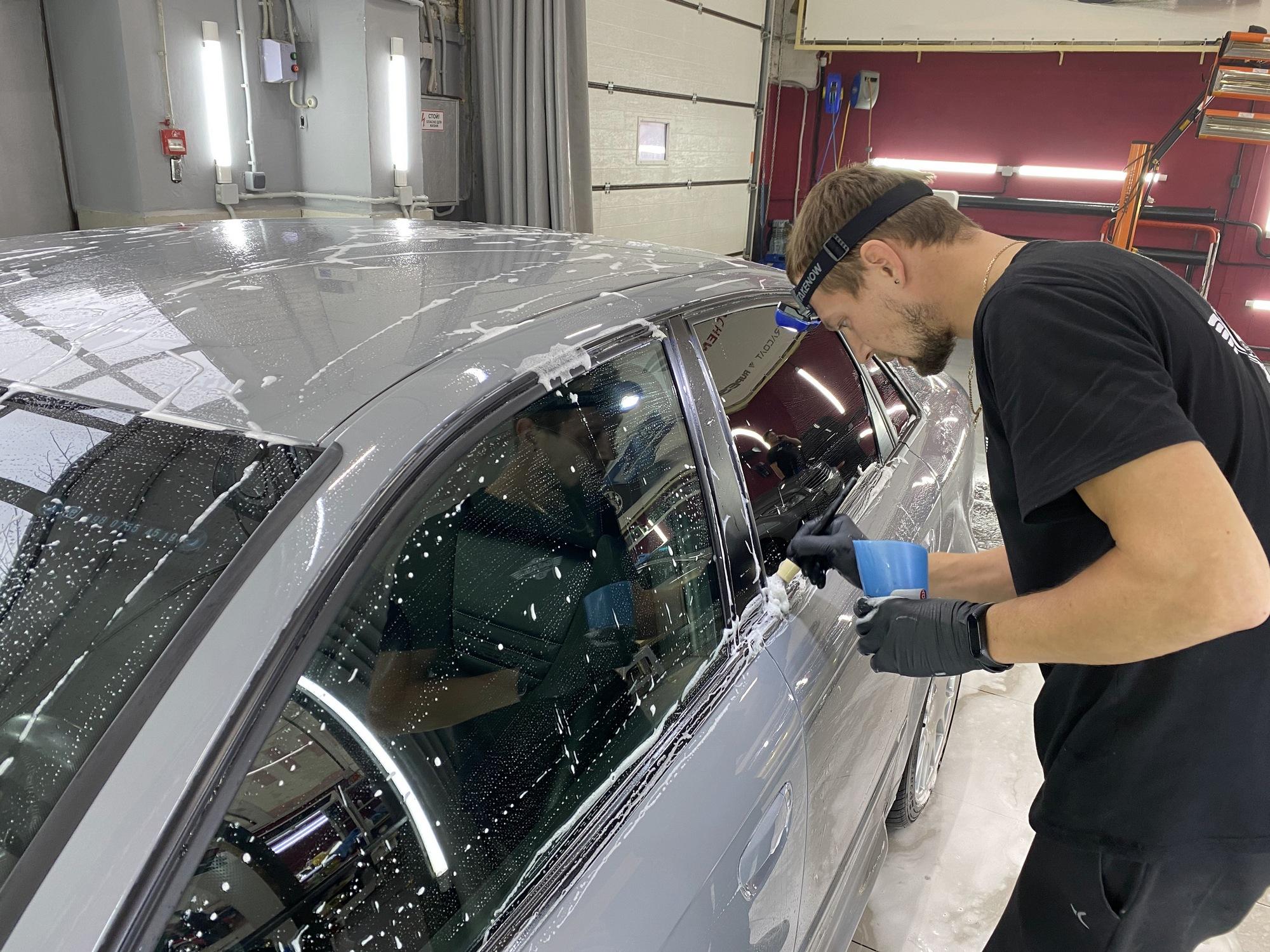 Мастер чистит дверь автомобиля кисточкой.