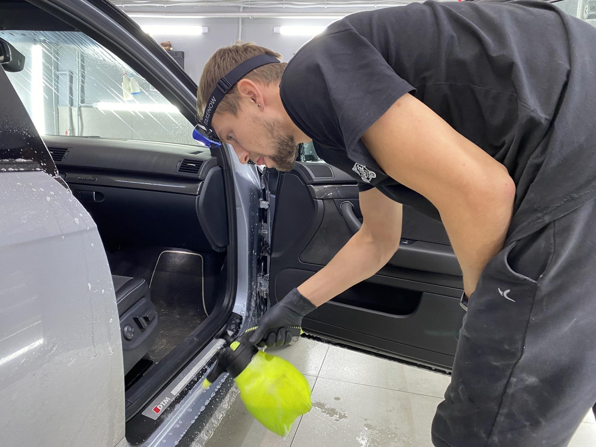 Смотреть на фото, как мастер моет порог дверного проема автомобиля.