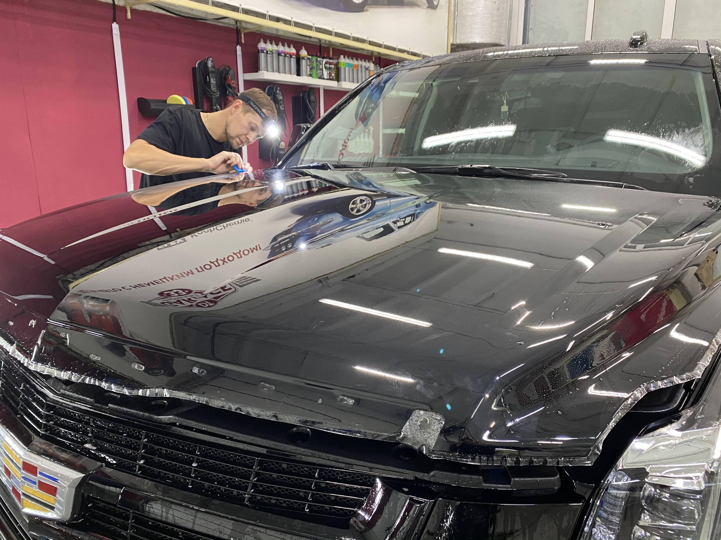 На фото крупным планом капот автомобиля Cadillac Escalade. Деталь оклеена пленкой PremiumShield.