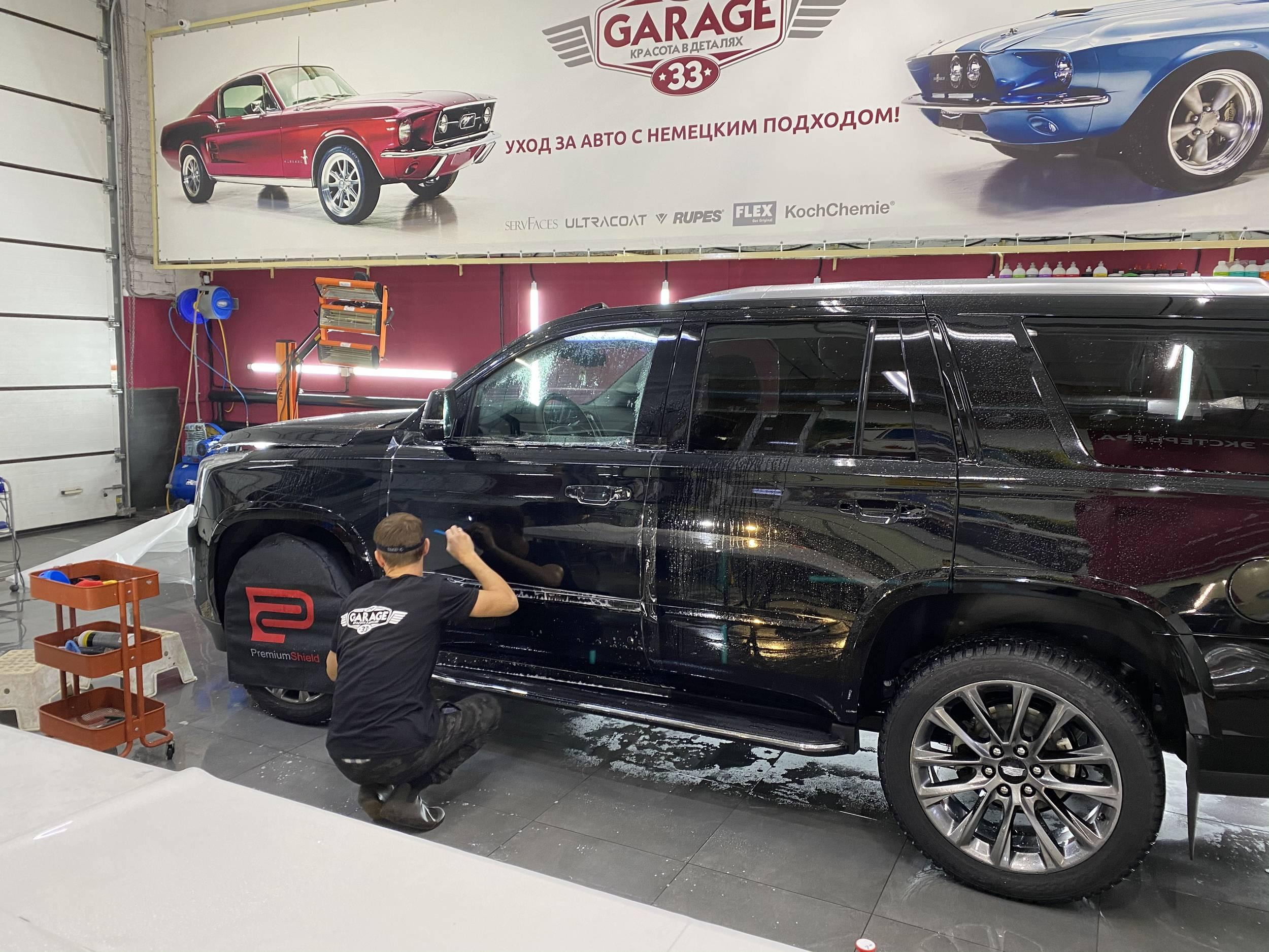 Смотреть на фото процесс оклейки водительской двери автомобиля Cadillac Escalade антигравийной пленкой.
