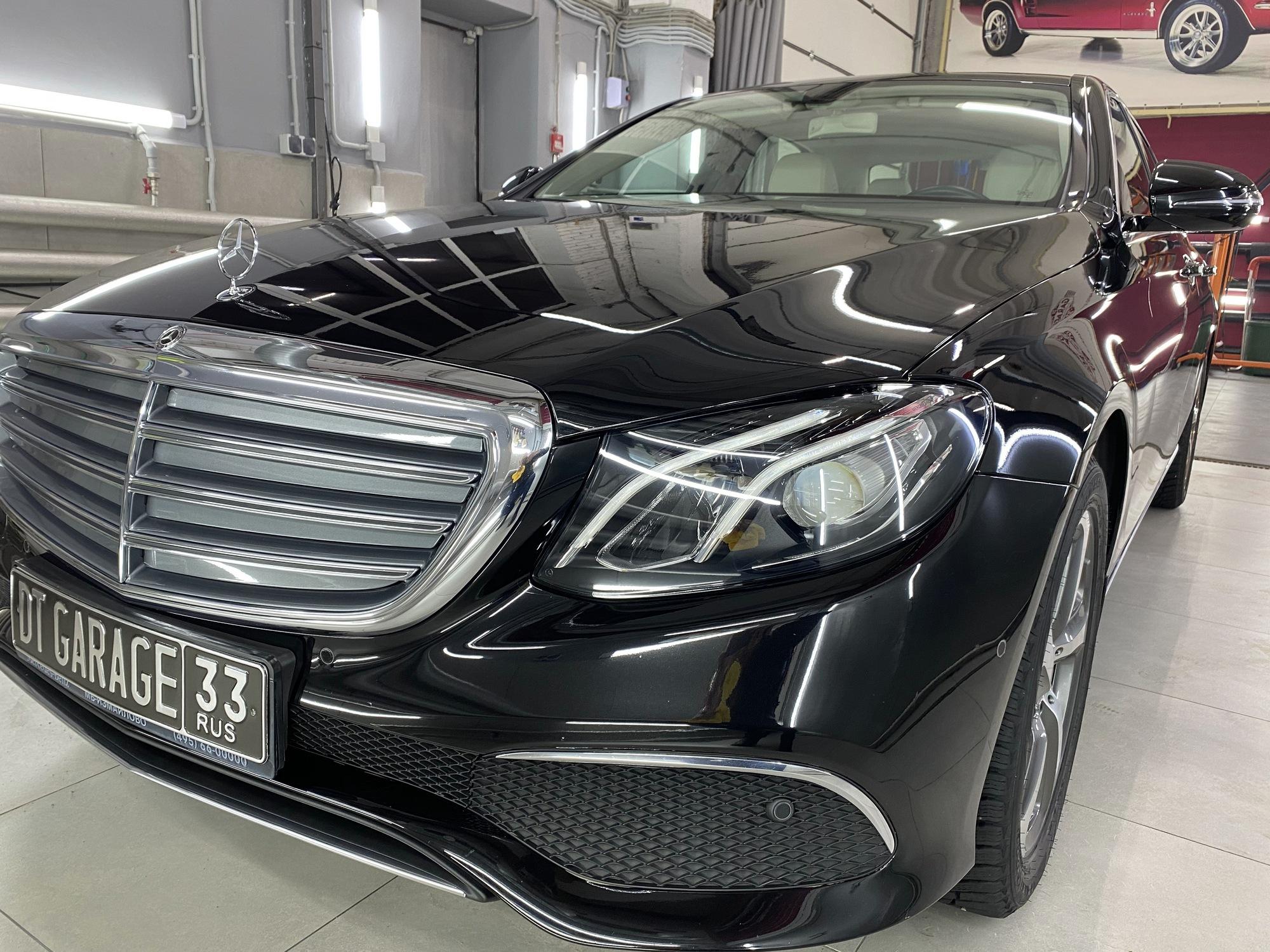 Смотреть черный автомобиль Mercedes Benz E-класс черного цвета под жидким стеклом.