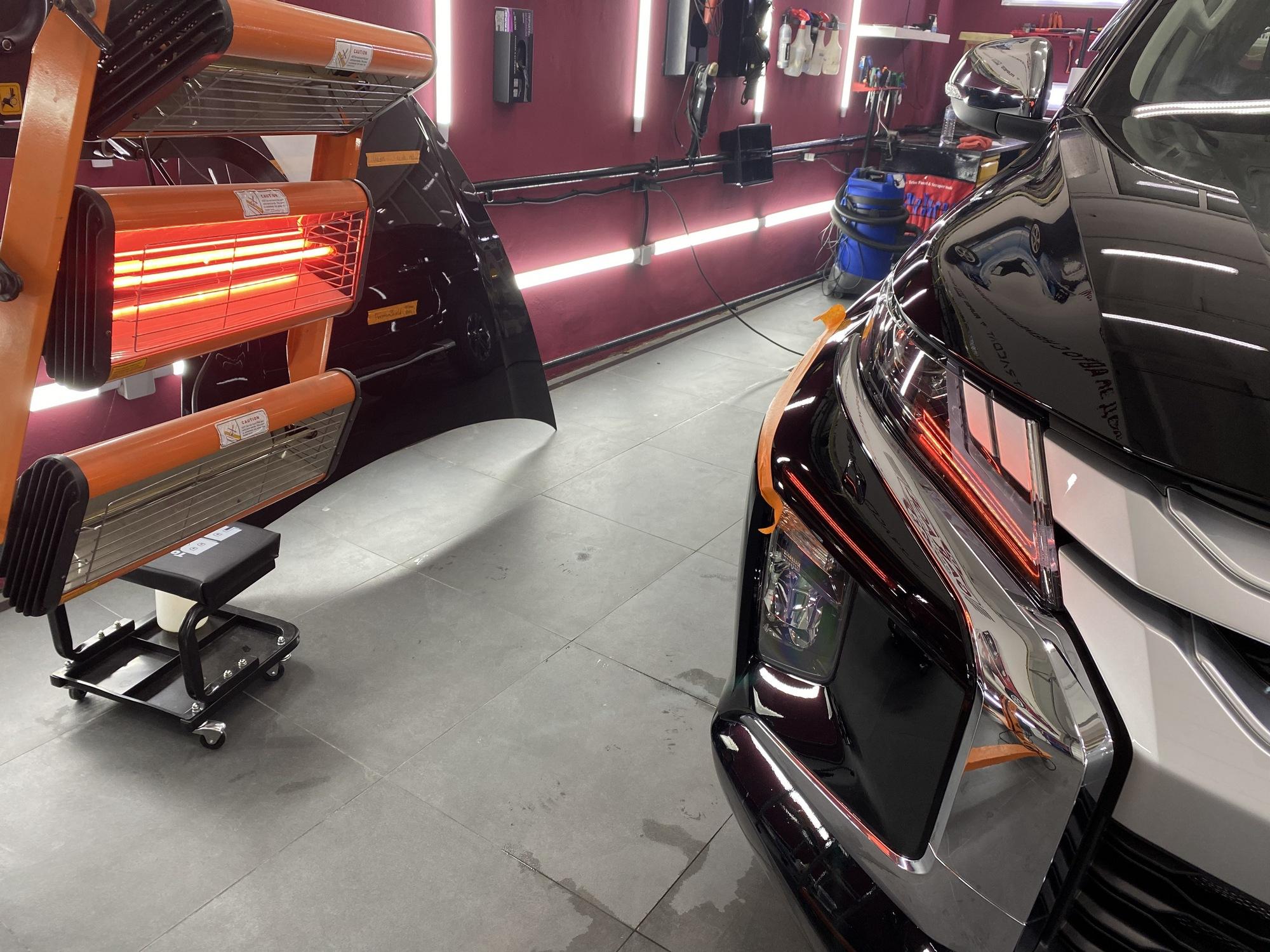 Смотреть на фото процесс просушки отреставрированного фрагмента бампера автомобиля.